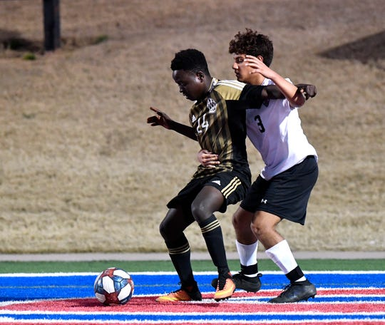 Abilene High's Dieudonne Miruho is held back by Haltom's Julyan Pinones during Tuesday's soccer match at Shotwell Stadium Feb. 26, 2019.
