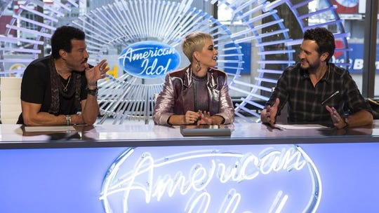 """American Idol"" judges Lionel Ritchie, left), Katy Perry and Luke Bryan hold the gold ticket in their hands."