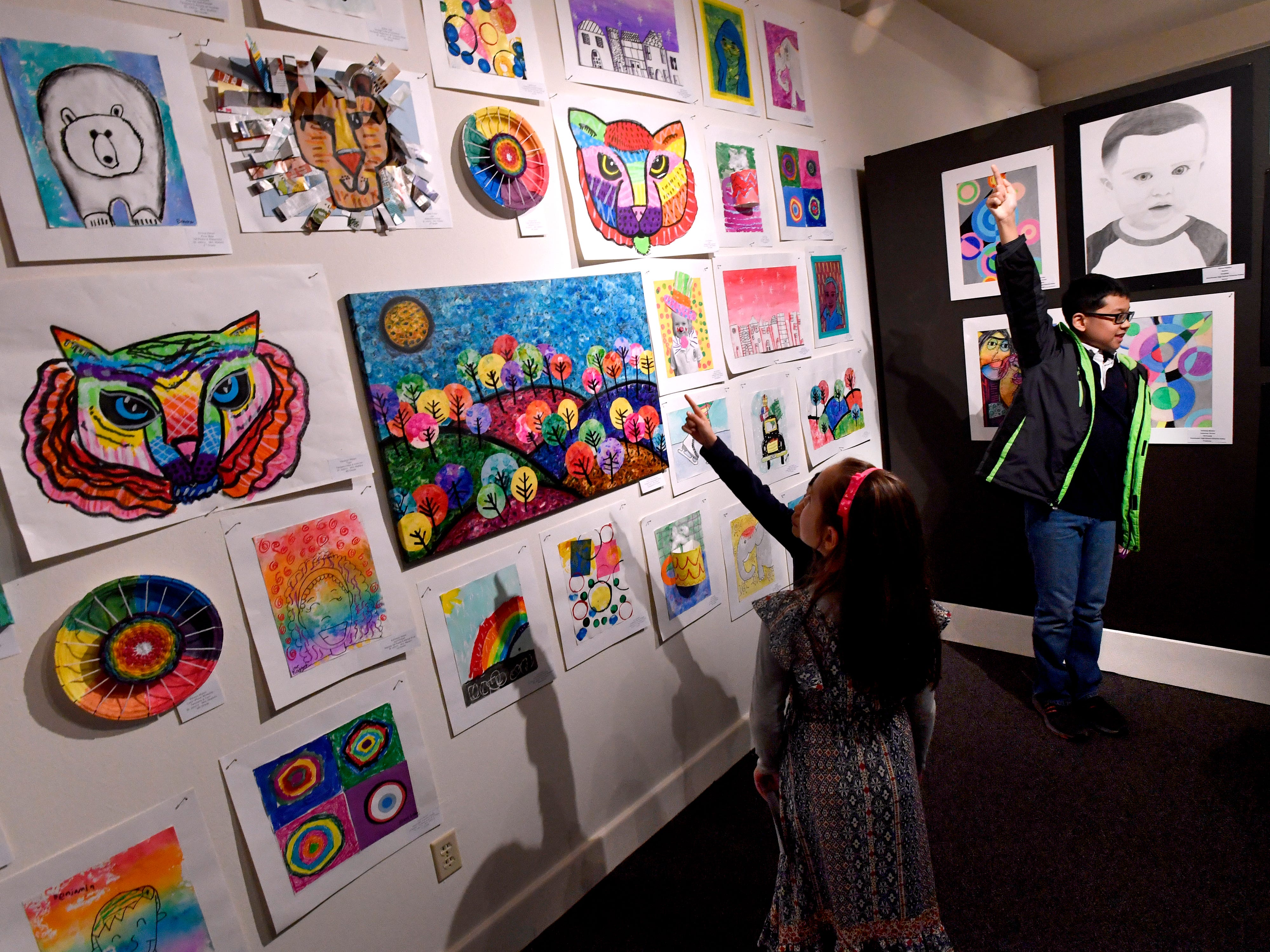 Children point to their artwork on display at the Grace Museum Feb. 21, 2019.