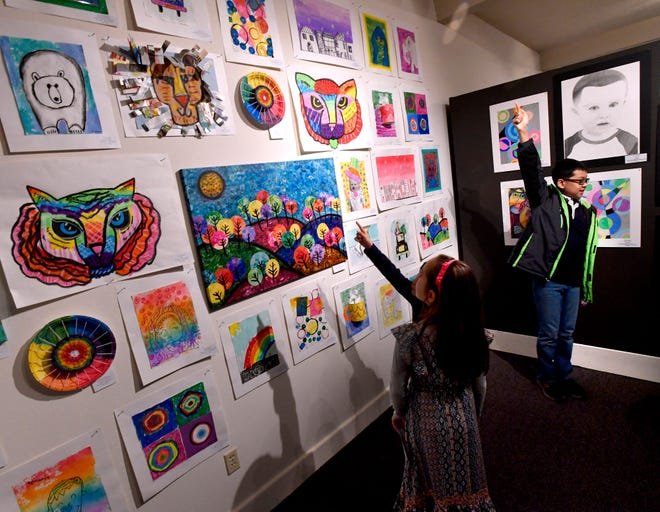 Children point to their artwork on display at The Grace Museum.