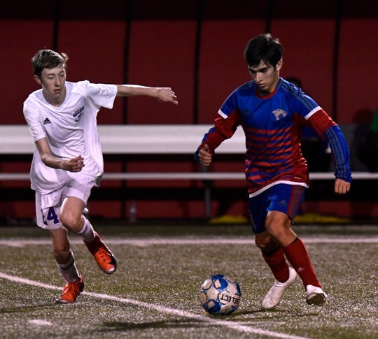 Wylie's Brett Carnes chases Cooper's Trey Castillo down the field during Tuesday's crosstown soccer match at Shotwell Stadium Feb. 26, 2019.