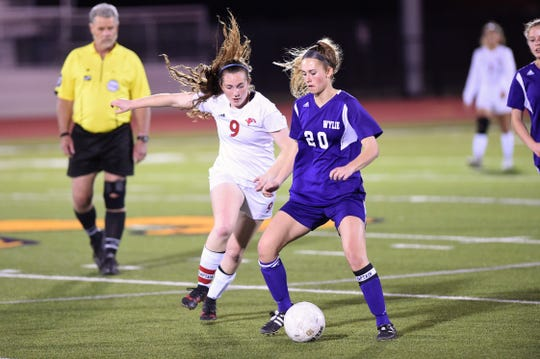 Wylie's Jacqueline Williams (20) holds off Cooper's Honna Turner (9) at Bulldog Stadium on Tuesday, Feb. 26, 2019. The Lady Cougars won 1-0.