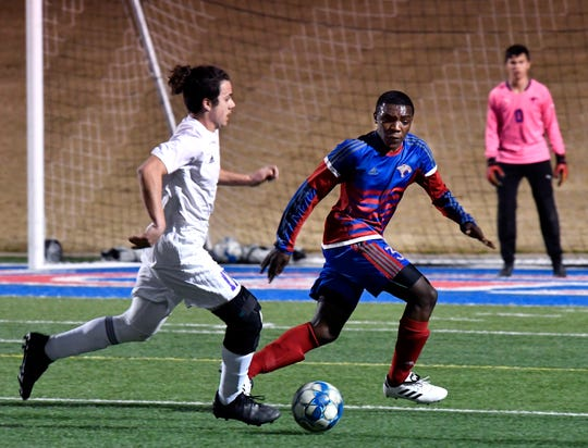 In this file photo from 2019, Waelongo Mrisho defends against Wylie High School's Peyton Wood during a crosstown soccer match. Mrisho is set to graduate, virtually, from Cooper High at noon Sunday.