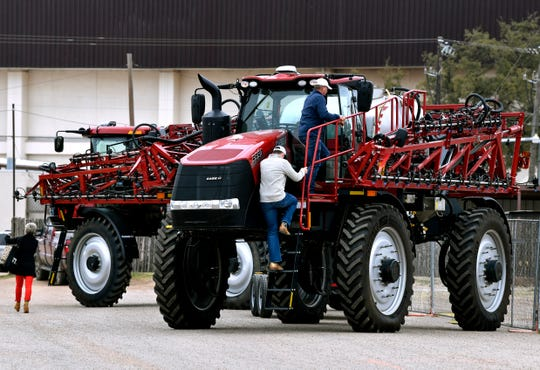Attendees walk past and inspect farm sprayers during the Texas Farm-Ranch-Wildlife Expo in the Taylor County Coliseum Feb. 19, 2019.