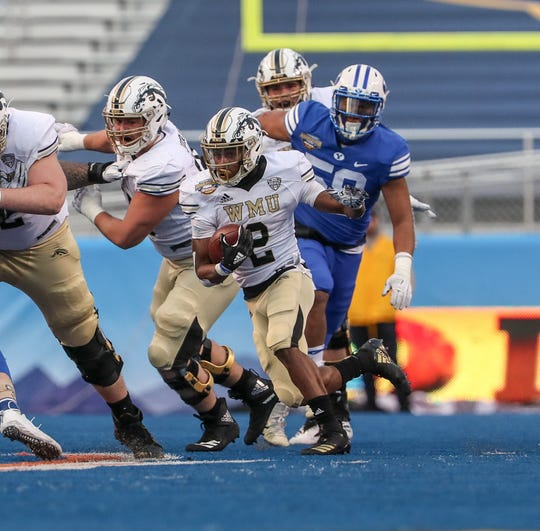 Running back LeVante Bellamy (2) of the Western Michigan Broncos finds space behind the block of Luke Juriga (52) against BYU in the 2018 Potato Bowl.