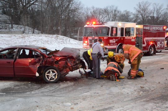 First responders treat a young woman after she was extricated from the wreckage.