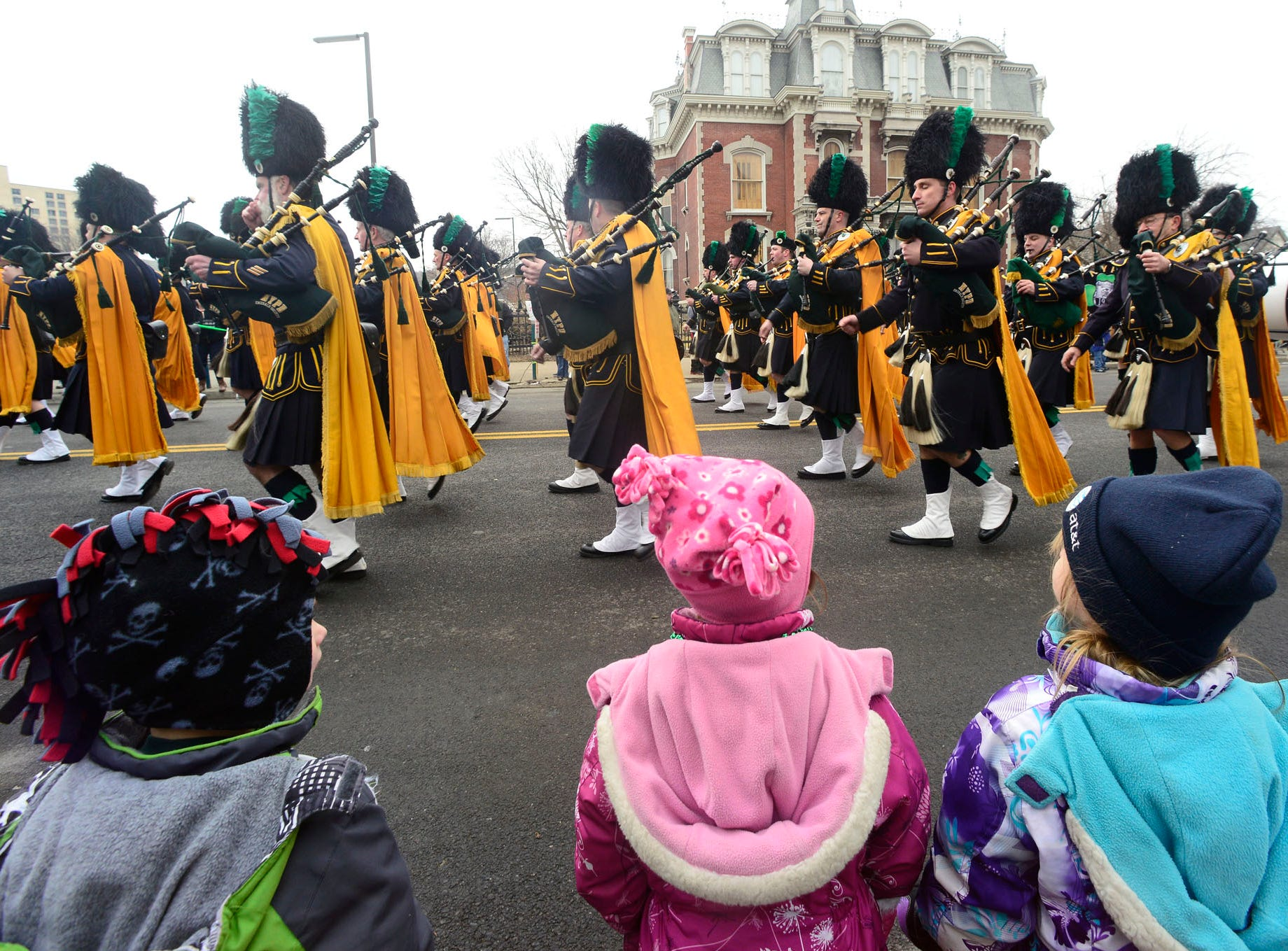 2013: Ryan Lewis, 4, right, Lauren Lewis, 4, Center, and Madi Lewis, 4, watches as the NYPD Pipes & Drums of the Emerald Society passes by during the St. Patrick's parade down Court Street in Binghamton on Saturday, March 2, 2013.