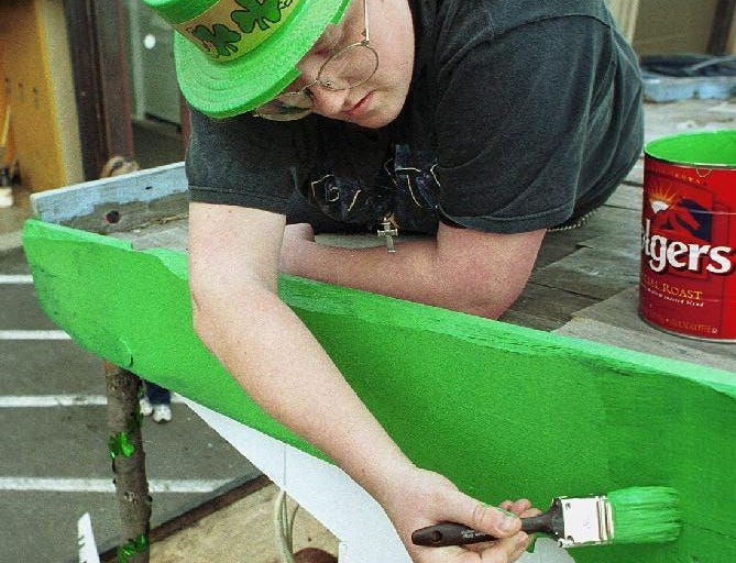1999: Jennifer Anthony, 17, of Owego put some finishing touches on the float members of BOCES Conservation program are entering in the St. Patricks Day parade.