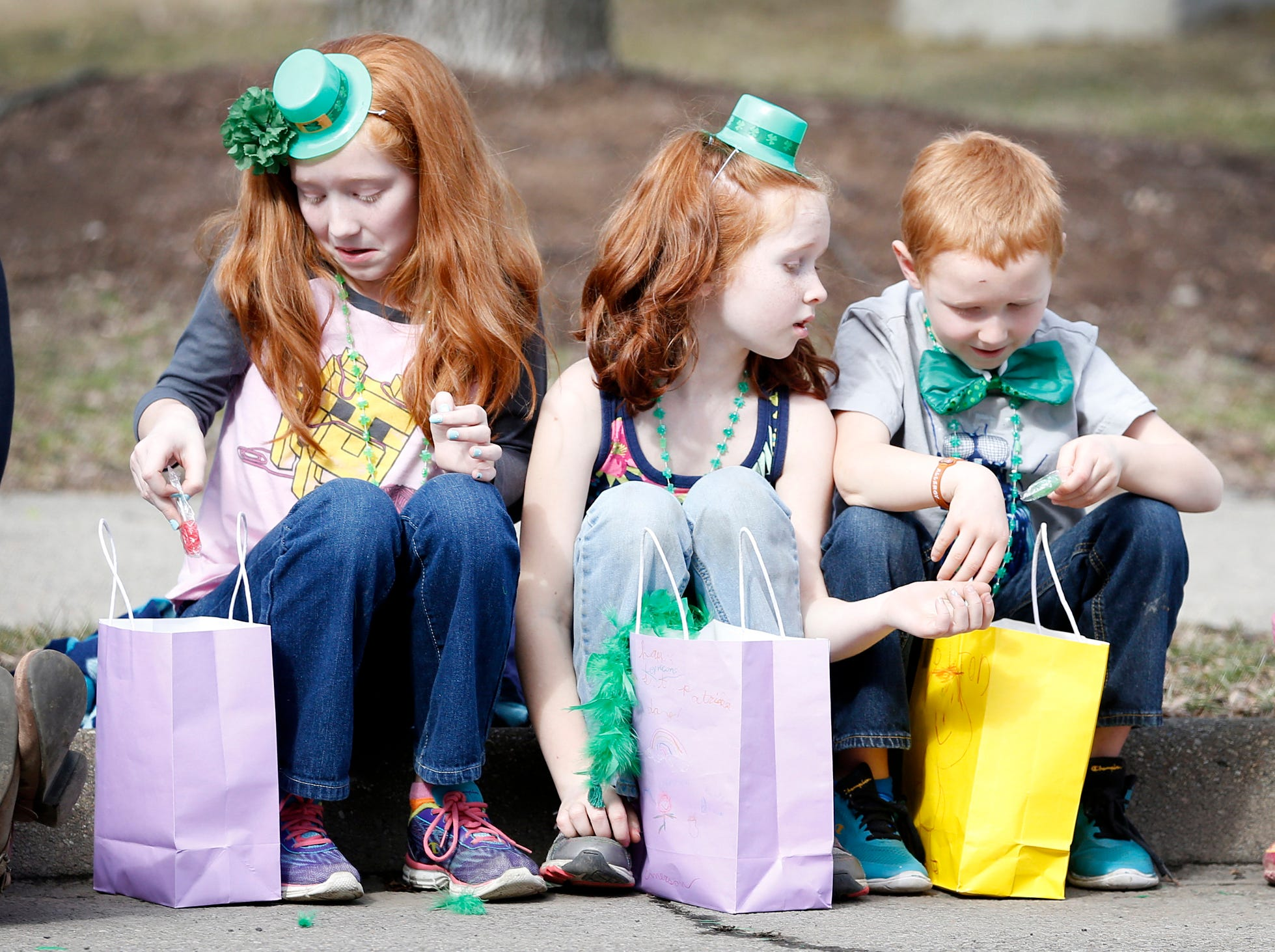 2016: Rhiannon Swimelar, 10, left, and her siblings Emerson, 8, and Colton, 6, all of Lowman, place candy in their bags that they recently grabbed during the St. Patrick's Day Parade Saturday.