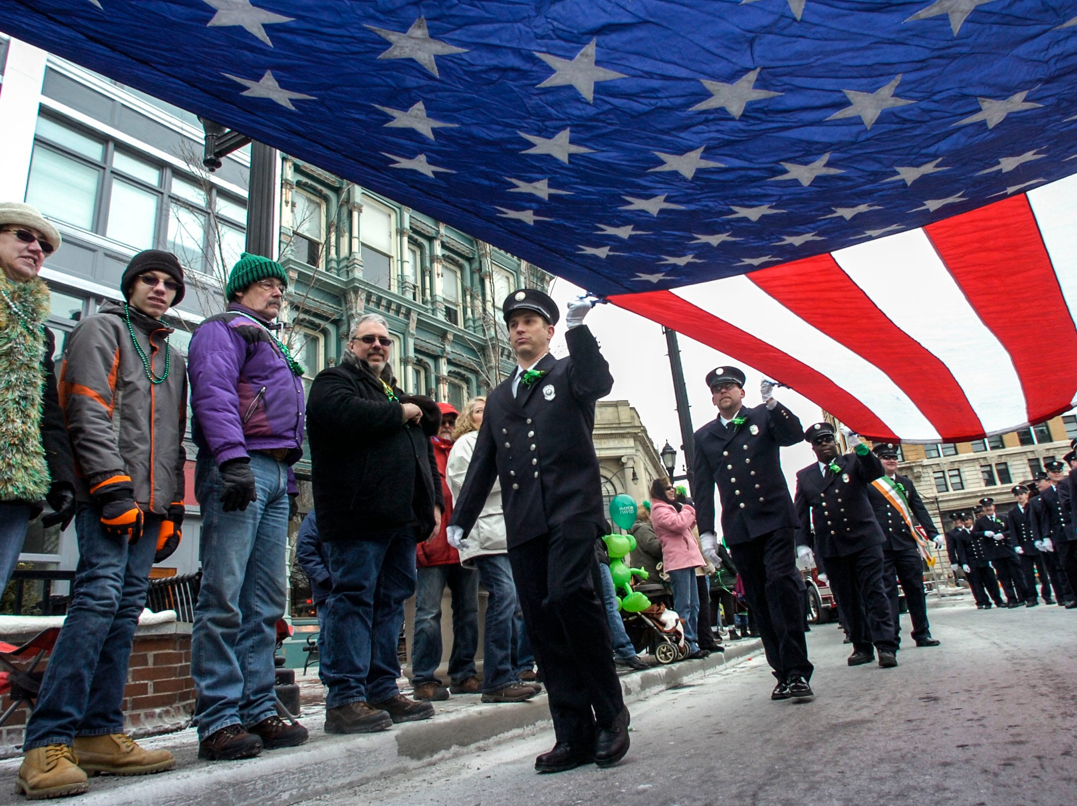 2014: Second Lt. Jason Stupski, from the Vestal Fire Department, and others carry an American Flag as they walk down Court Street during the 47th annual St. PatrickÕs Day Parade in downtown Binghamton on Saturday.