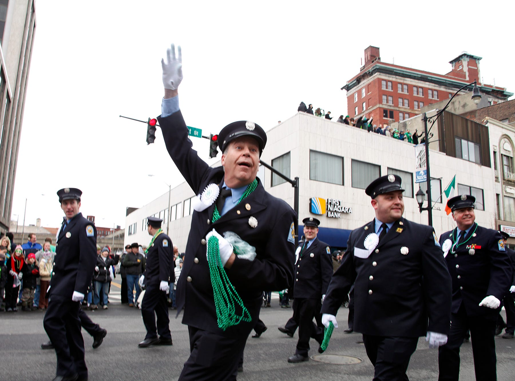 2013: Binghamton Firefighter John Janos tosses green beads to parade attendees, on Court Street, during the St. Patrick's Day Parade, held on Saturday afternoon, in downtown Binghamton.
