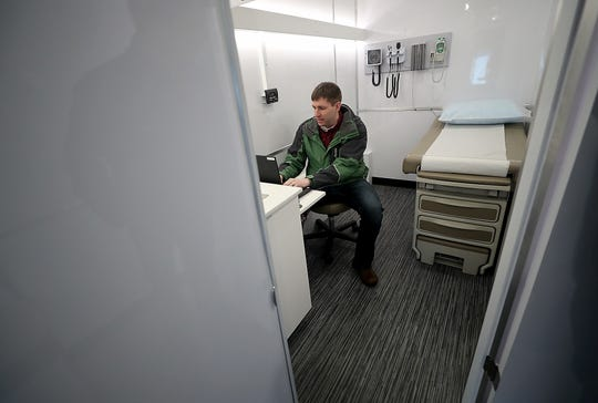 Anthony Lyon-Loftus, with Peninsula Community Health Services, opens up the computer work station in of the exam rooms inside the mobile primary care unit.