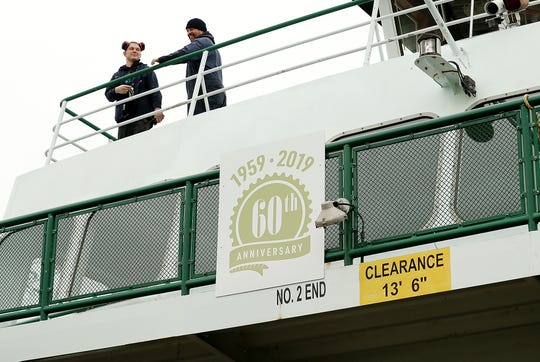 A pair of Eagle Harbor Maintenance Facility crew members stand on the deck above the newly placed 60th anniversary sign aboard the Washington State Ferry Tillikum on Wednesday.