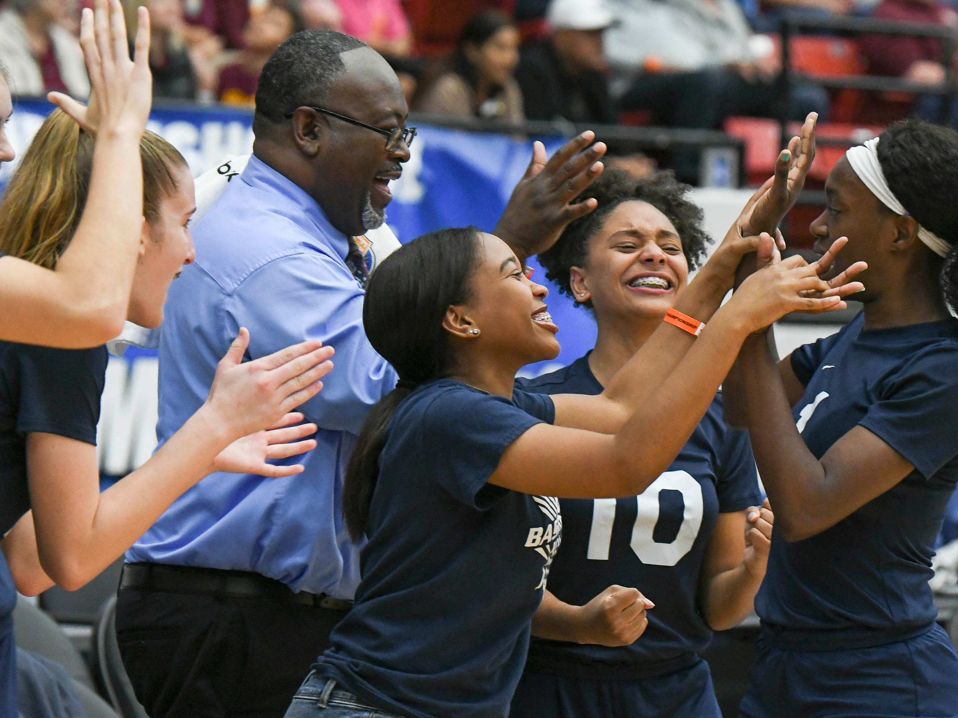 Florida Prep players congratulate Jayla Johnson as she comes to the bench late in Tuesday's Class 2A state championship game against Bayshore Christian.
