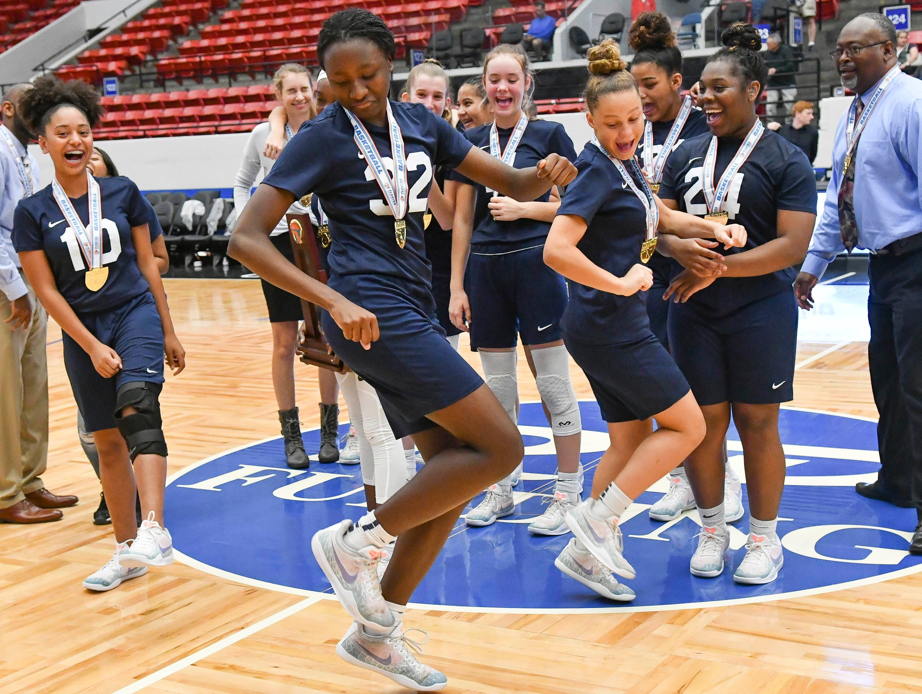 Paige McDonald (32) and the Florida Prep Falcons celebrate their victory in Tuesday's Class 2A state championship game.