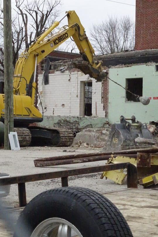 Dave Allen, owner of Allen Excavating of Bloomville, swings a wrecking ball as demolition work continues at the city's old water treatment plant on Wednesday morning.