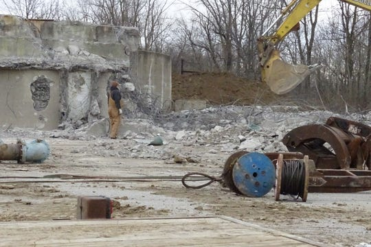 Workers from Allen Excavating of Bloomville continue demolition work at the city's old water treatment plant on Wednesday morning.