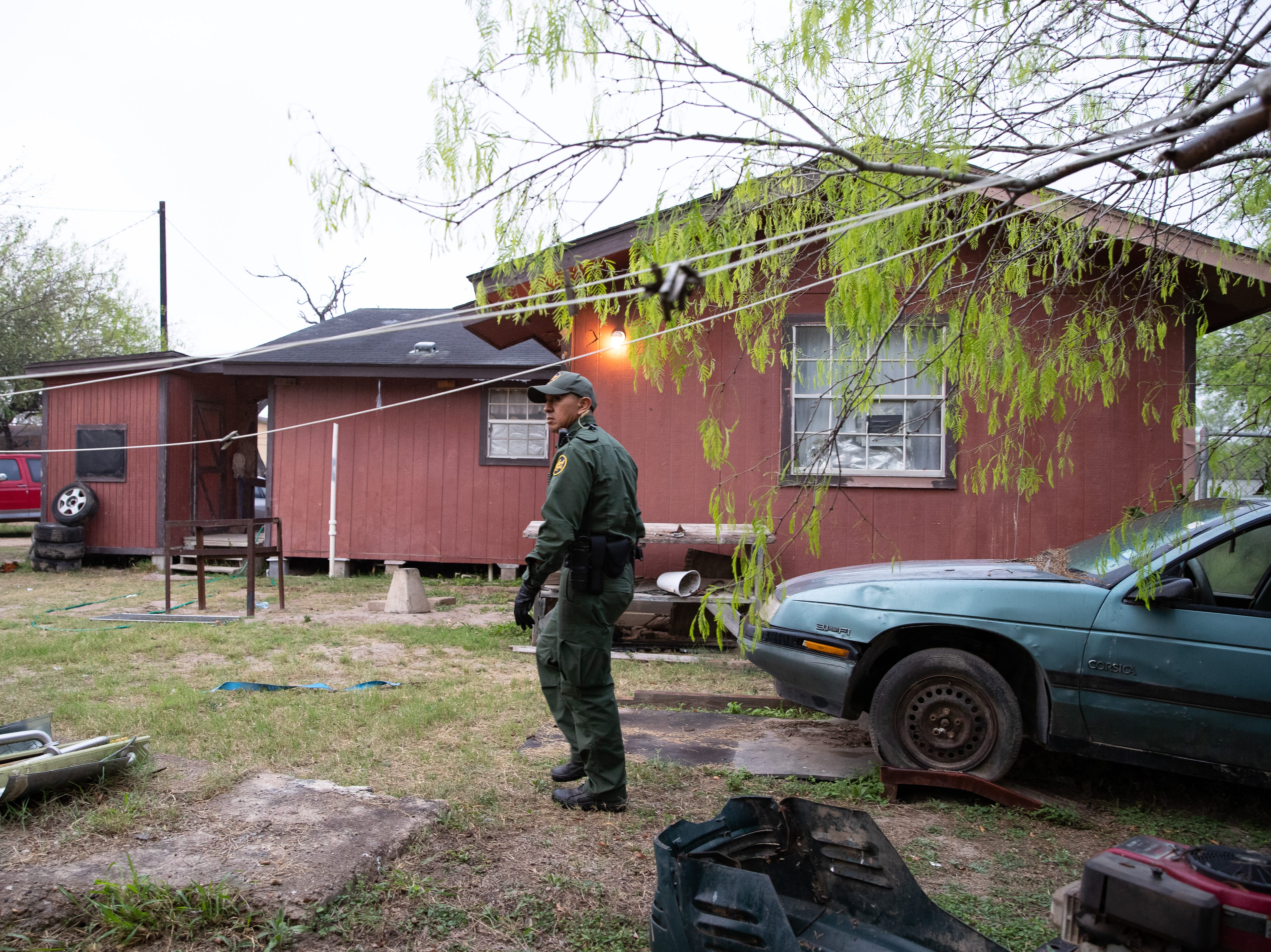 Border Patrol Agent Hermann Rivera searches the backyard of a home in Penitas, Texas, after a camera spotted two  migrants walking in the area on Tuesday, Feb. 28, 2019.