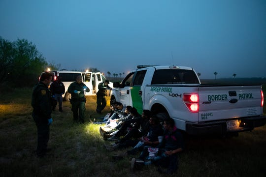 Border Patrol agents take a group of migrants in to custody  near Mission, Texas, after tracking them though a field on Tuesday, Feb. 26, 2019.