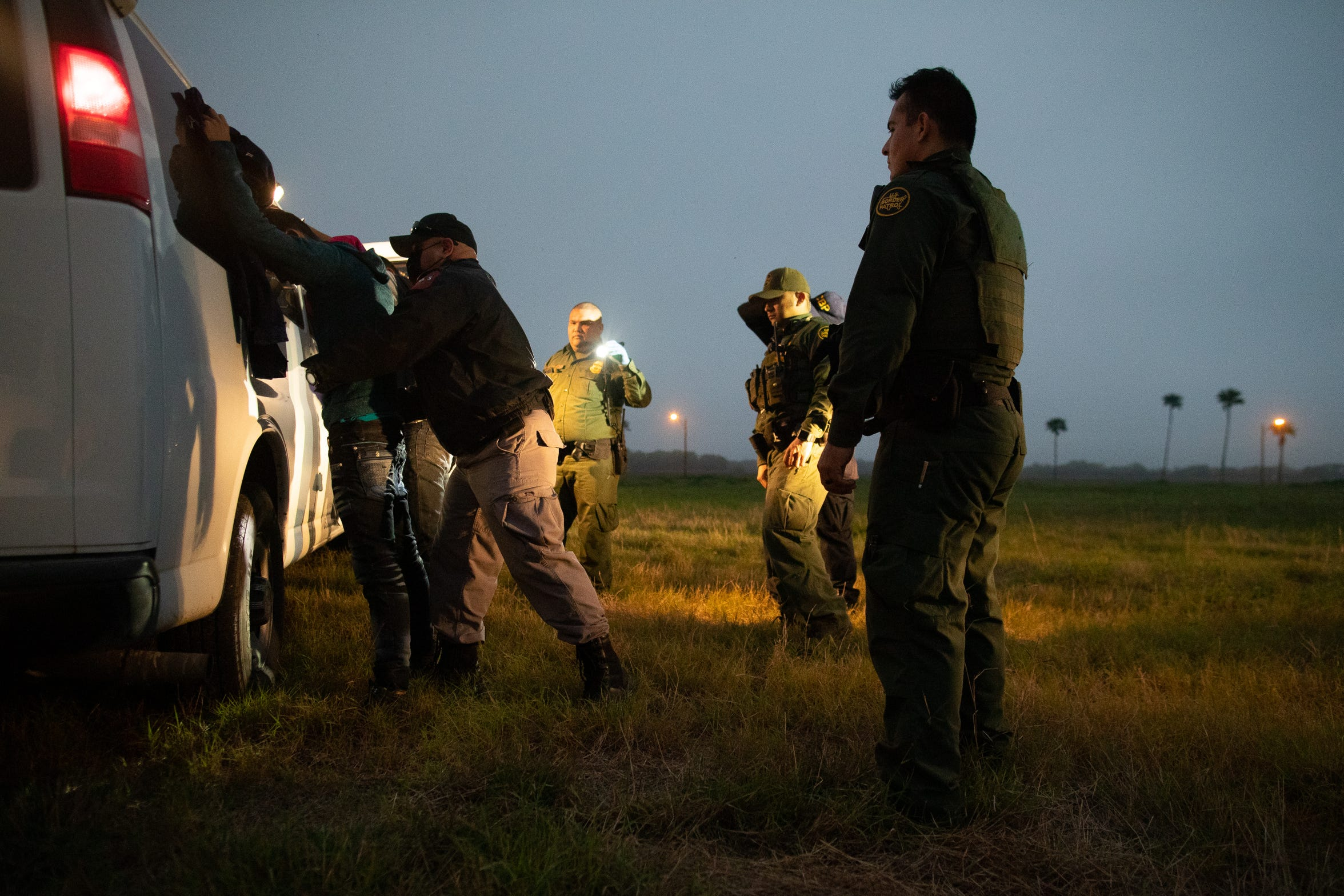 A migrant is searched before being transported after being taken in to custody by Border Patrol near Mission, Texas, after tracking them trough a field on Tuesday, Feb. 29, 2019.