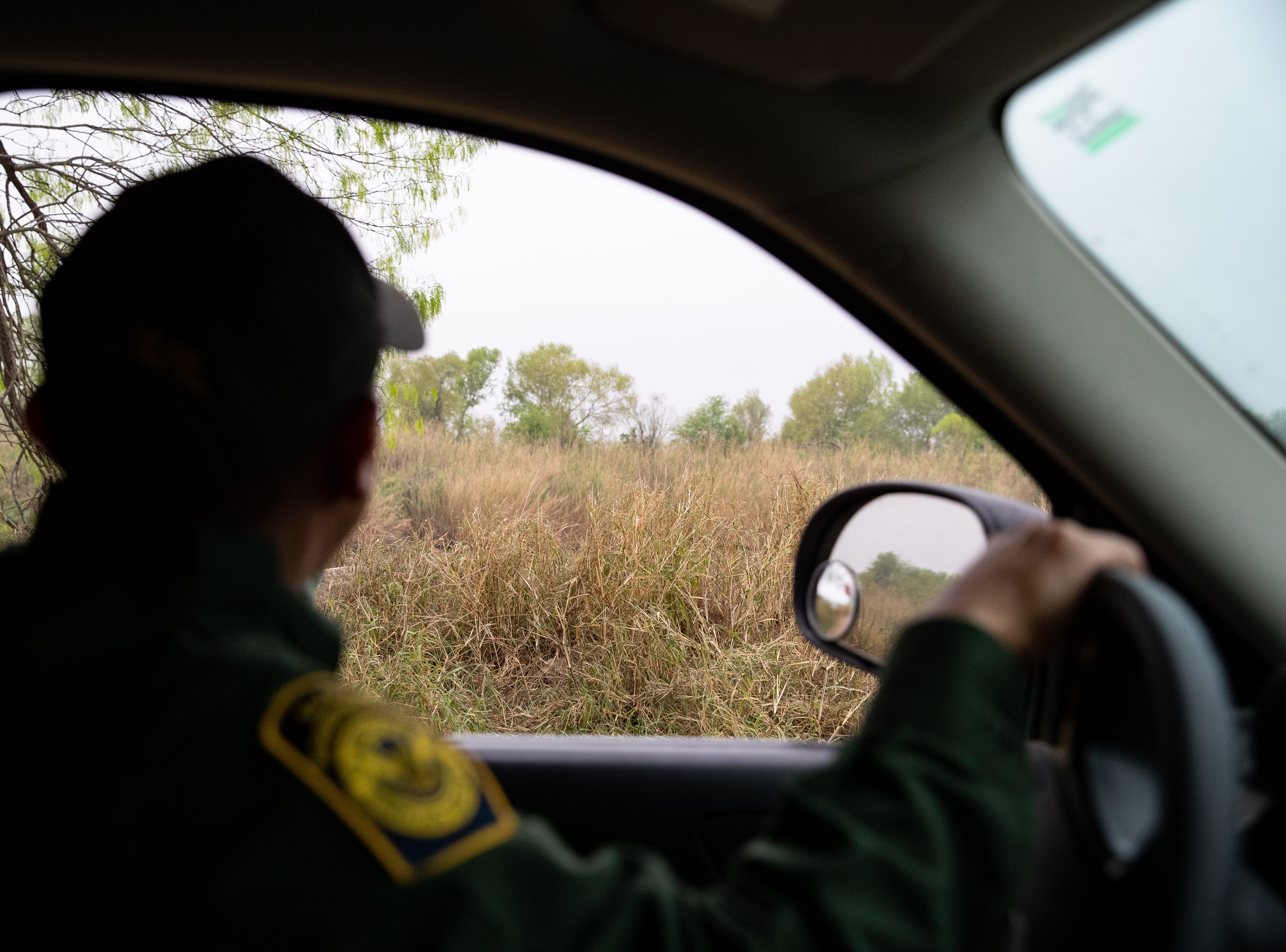 Border Patrol Agent Hermann Rivera looks as he drives past a field as other agents as other agents on foot search an area in Penitas, TX  for migrants spotted running in the area on Tuesday, Feb. 26, 2019.