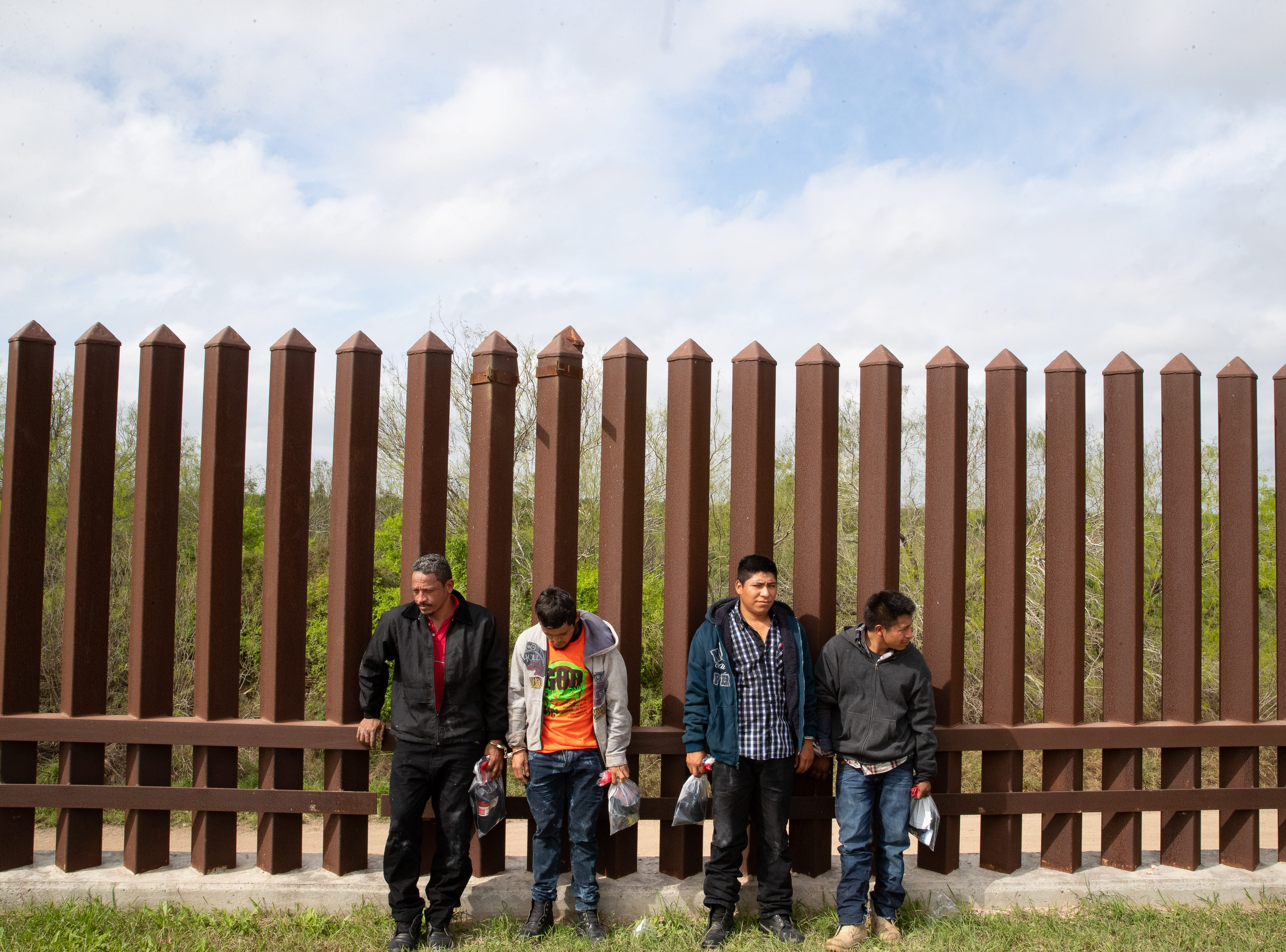 Four migrants stand along the bollard border fence in Mission TX, after being taken in to custody by Border Patrol on Tuesday, Feb. 28, 2019.