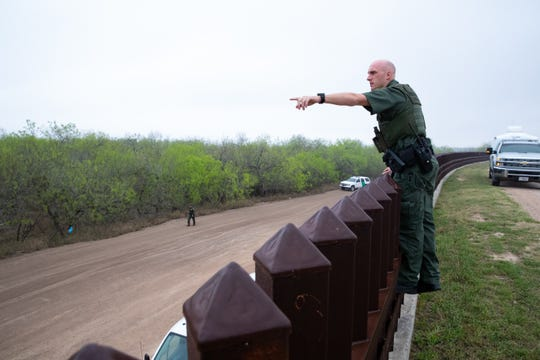 A Border Patrol Agent standing along the border wall near Panitas, TX, points to a spot in the brush after migrants trying to use a ladder where spotted on camera on Tuesday, Feb. 28, 2019.