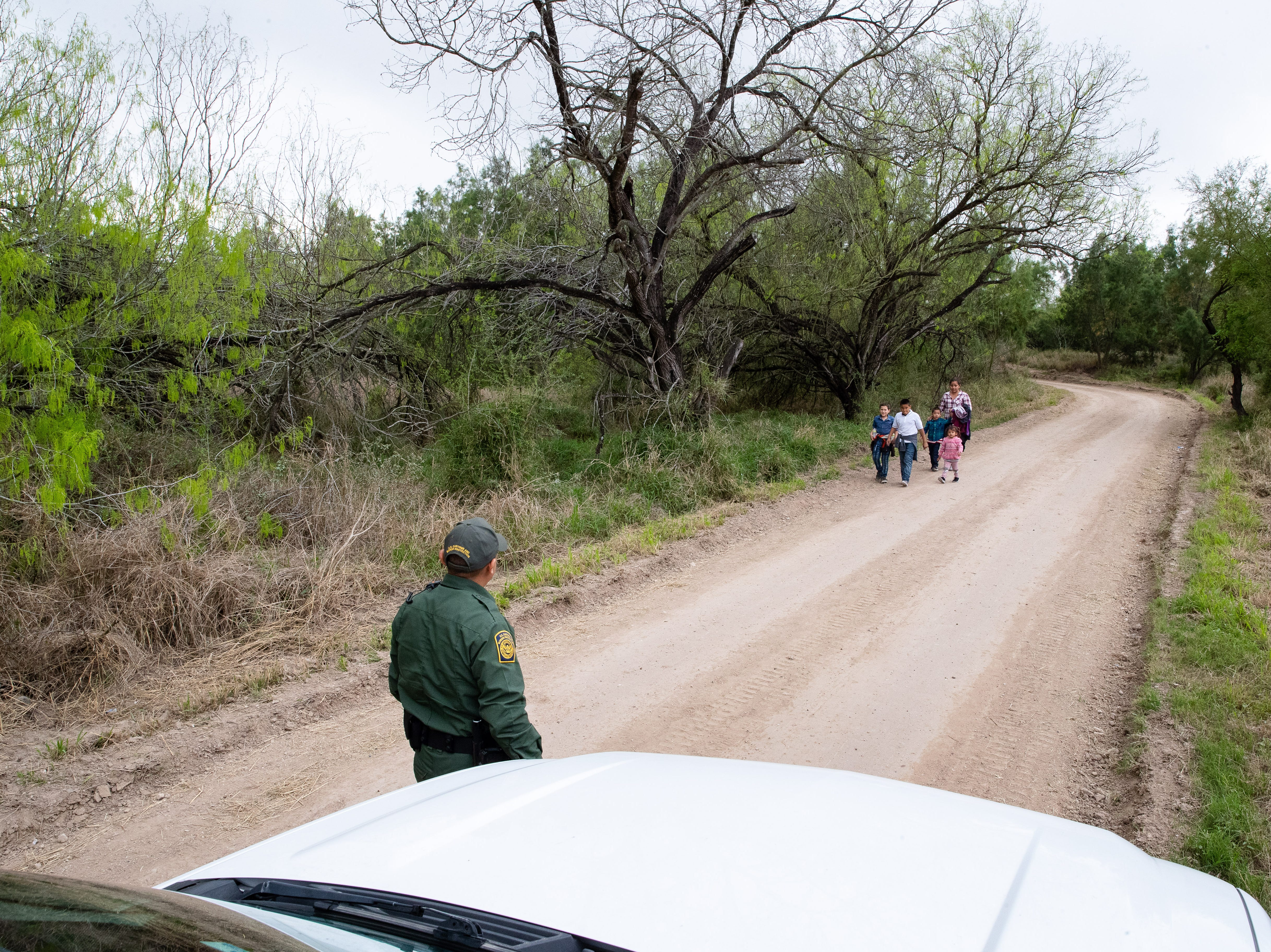 Border Patrol Agent Hermann Rivera approaches a group of migrants along a dirt road near Mission, Texas, on Tuesday, Feb. 28, 2019.