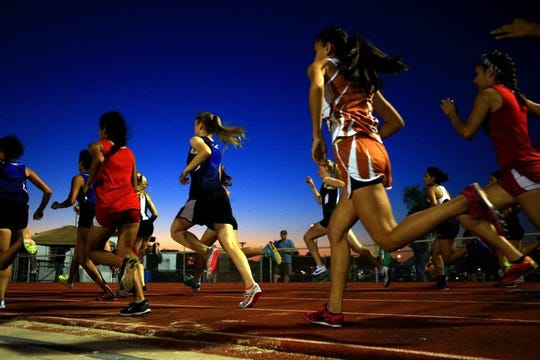 Girls run during the District 31-4A track meet in Sinton.