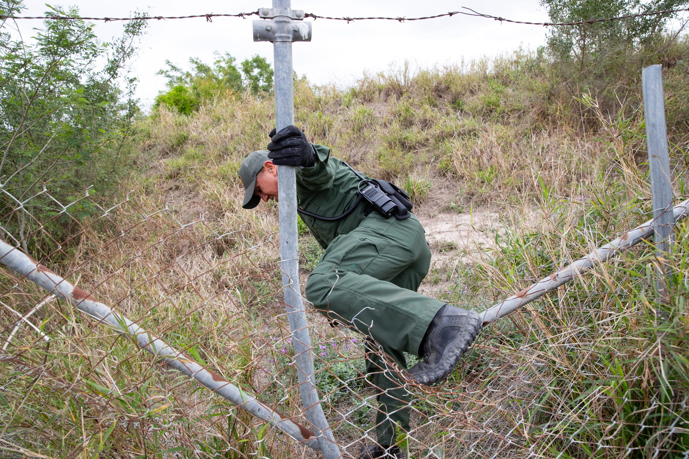 Border Patrol Agent Hermann Rivera climbs through a fence as he assists other agents searching an area in Mission, Texas, for five migrants who ran from agents on Tuesday, Feb. 28, 2019.