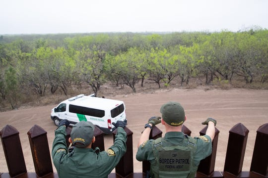 Border Patrol agents standing along the border wall near Penitas, Texas, look down at other agents after taking two migrants in to custody on Tuesday, Feb. 26, 2019.