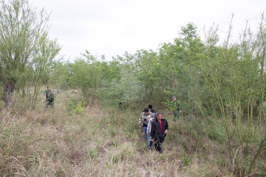 Border Patrol agents take a group of migrants in to custody  after they ran in to a filed in Mission, Texas, on Tuesday, Feb. 26, 2019.