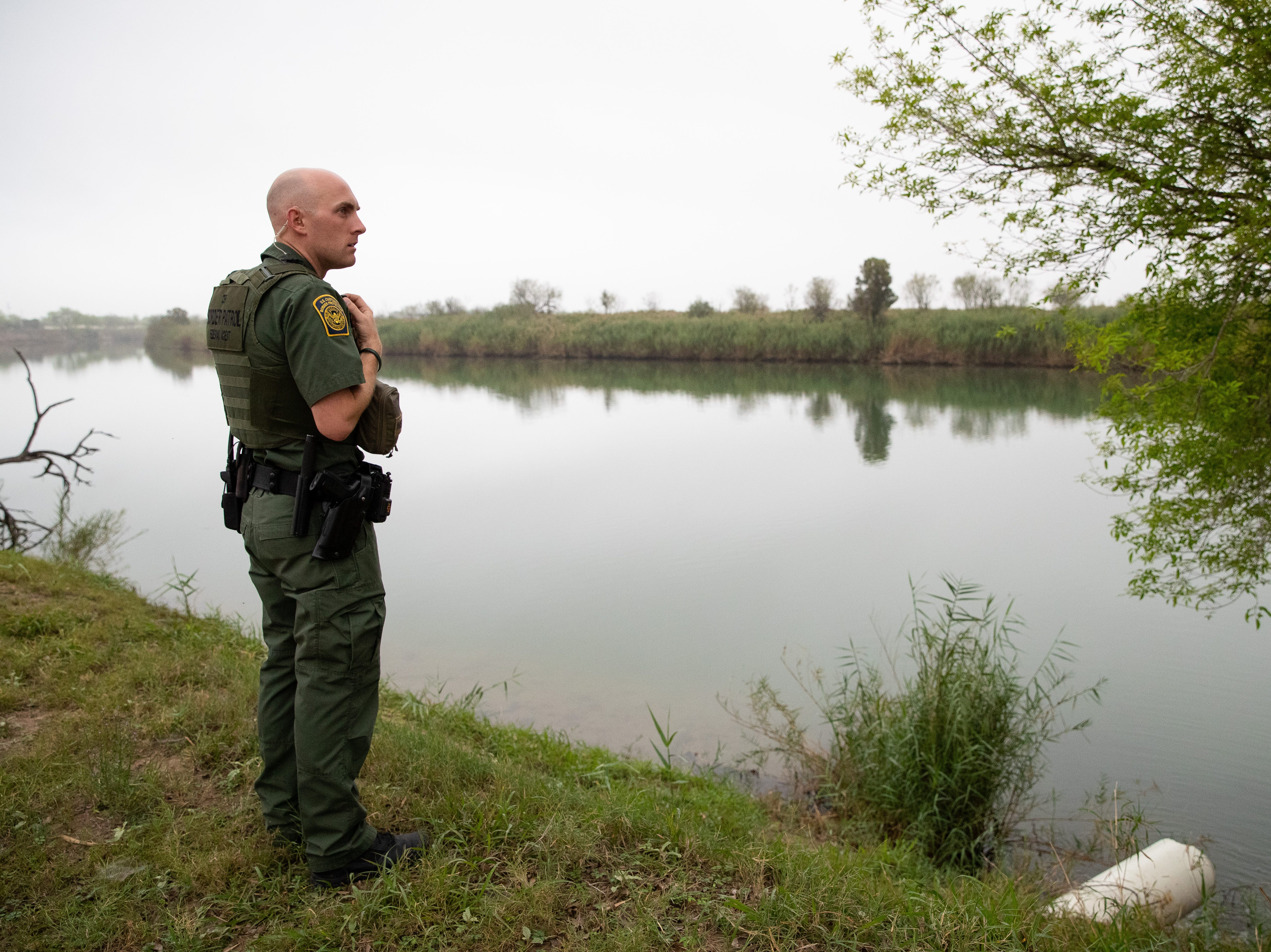 A Border Patrol Agent over looks the Rio Grande River in to Mexico after a report of raft in the river near Penitas, TX on Tuesday, Feb. 26, 2019.