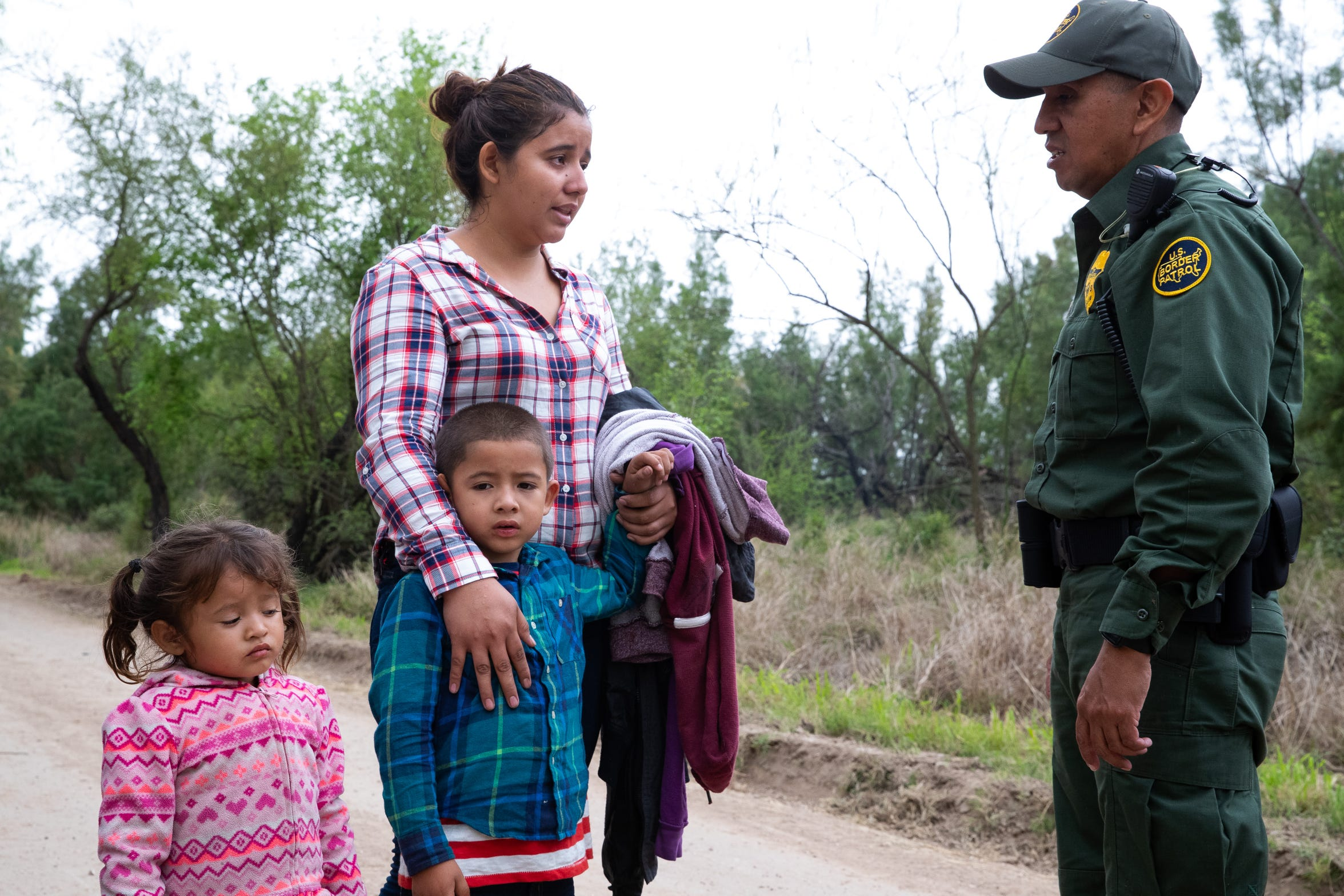 Border Patrol Agent Hermann Rivera talks with a 22-year-old women from El Salvador and her 5 and 3-year-old children after crossing the Rio Grande Valley from Mexico near Mission, Texas, on Tuesday, Feb. 26, 2019.