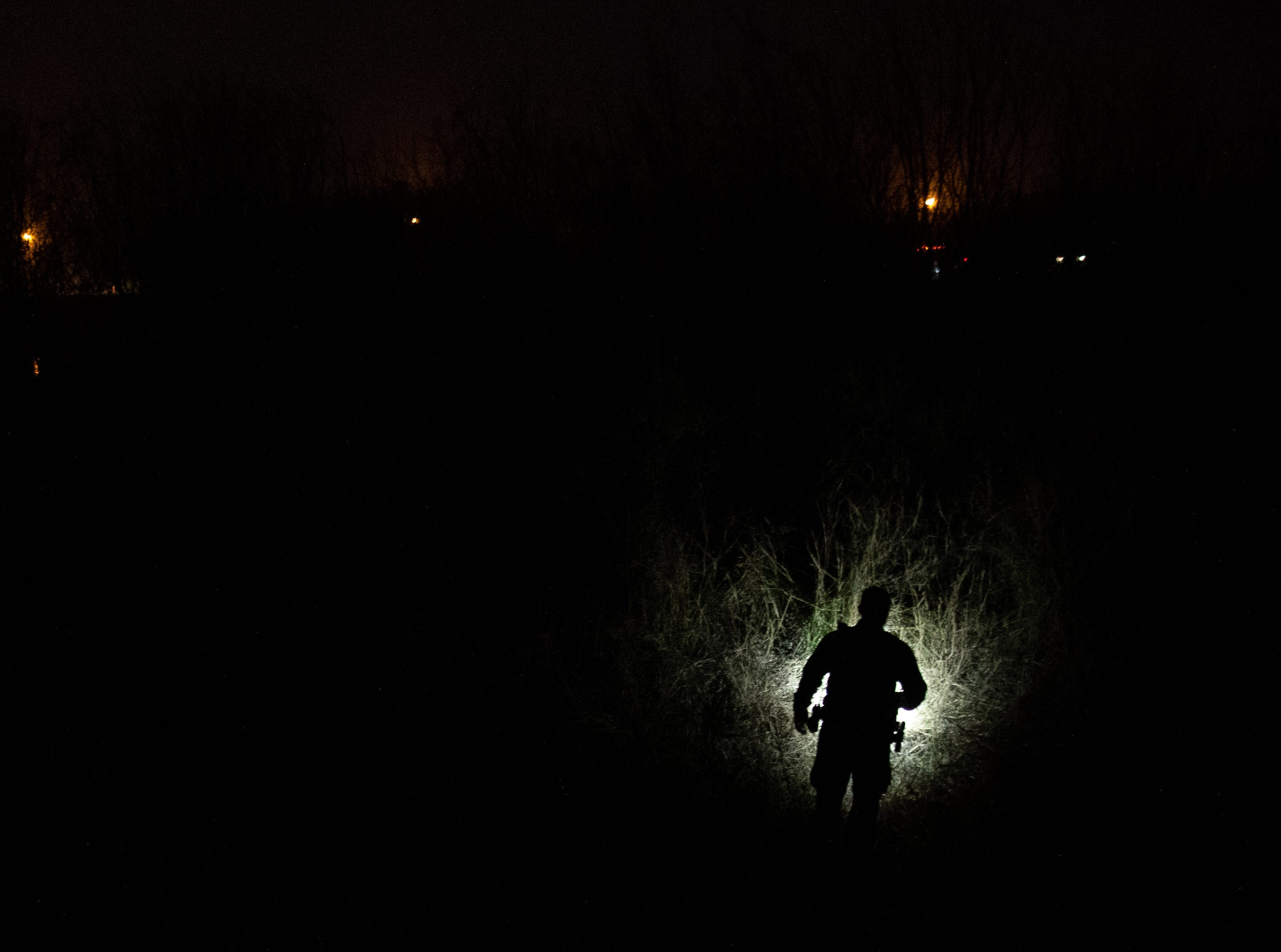 A Border Patrol agent searches an area for a group of migrants spotted running in to a field near Mission, Texas, on Tuesday, Feb. 26, 2019.