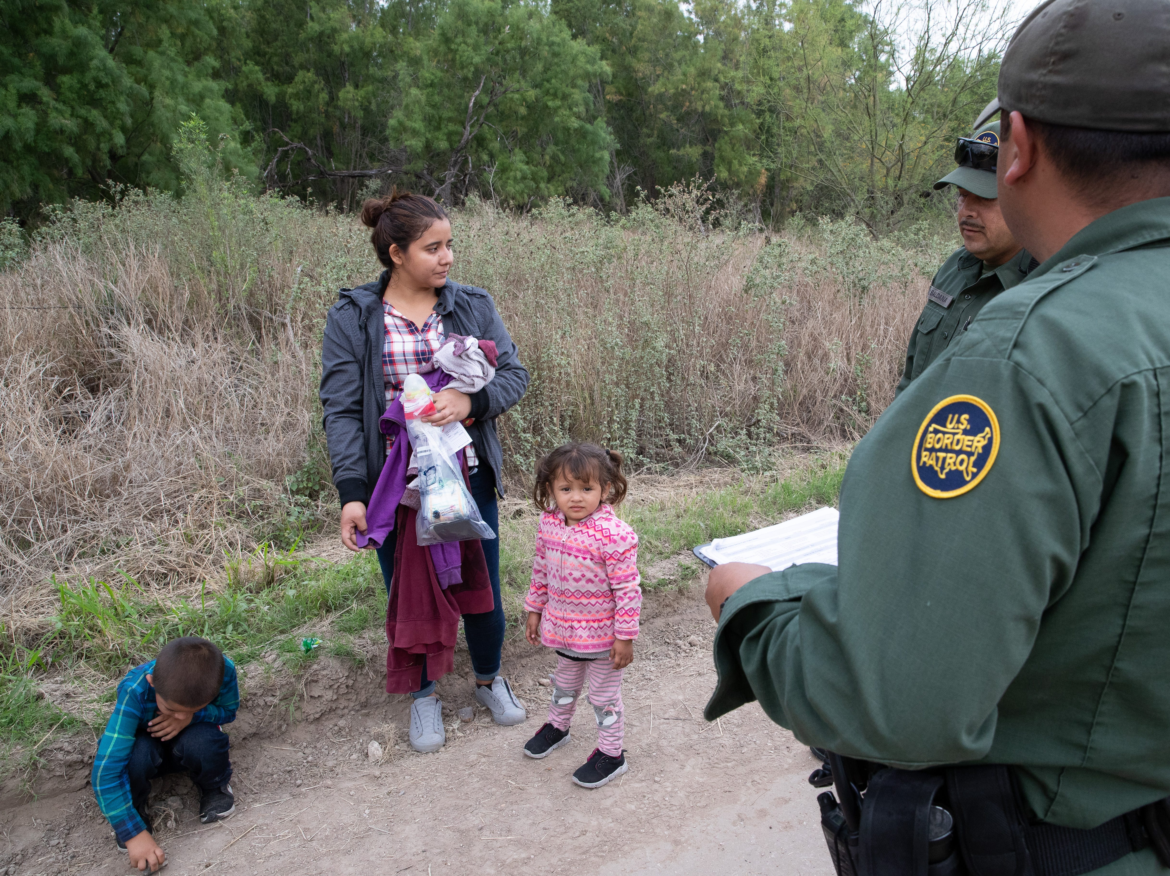 Border Patrol Agents take in to custody a 22-year-old women from El Salvador and her 5 and 3-year-old children after crossing the river from Mexico near Mission, Texas, on Tuesday, Feb. 26, 2019.