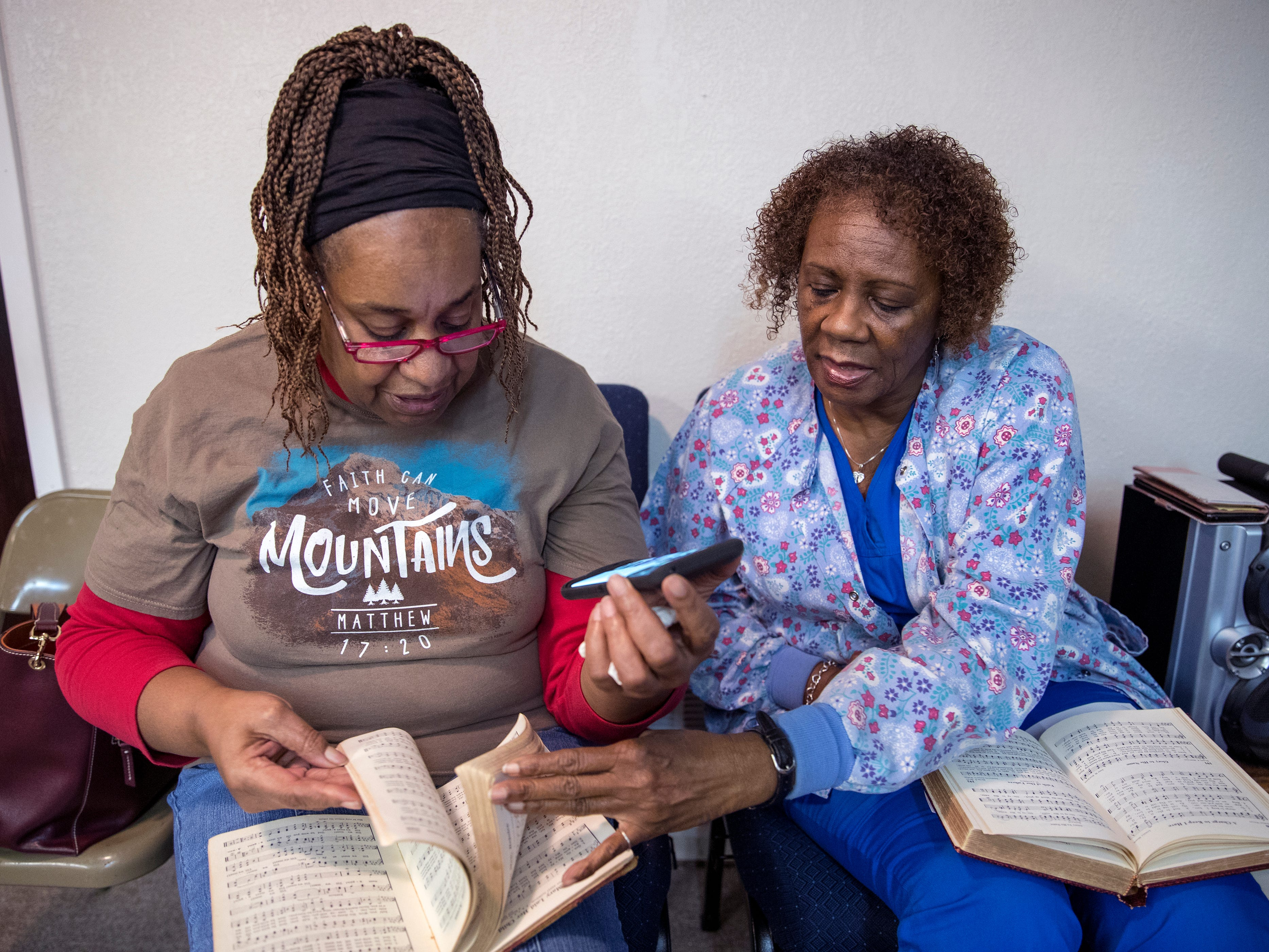 Jocelyn Etti (left) and Hattie McKnight search for music for songs to sing during a choir rehearsal at St. Paul Missionary Baptist Church in Rockport on February 2, 2019. The church is one of dozens of churches and other houses of worship that sought help from the federal government in the aftermath of Hurricane Harvey. This is the first disaster in which houses of worship have been eligible for public assistance under the Federal Emergency Management Agency.