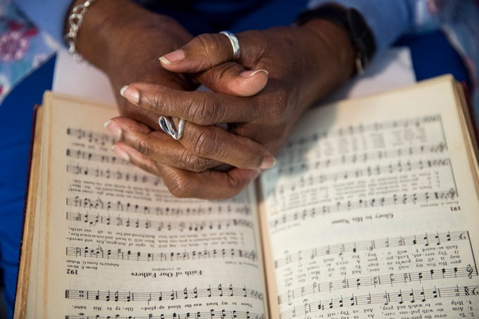 Hattie McKnight clasps her hands together as she sings during a choir rehearsal at St. Paul Missionary Baptist Church in Rockport on February 2, 2019. About 18 months after Hurricane Harvey caused major damage to homes, churches and houses of worship, dozens of religious congregations are looking to the federal government to help restore the faith community.