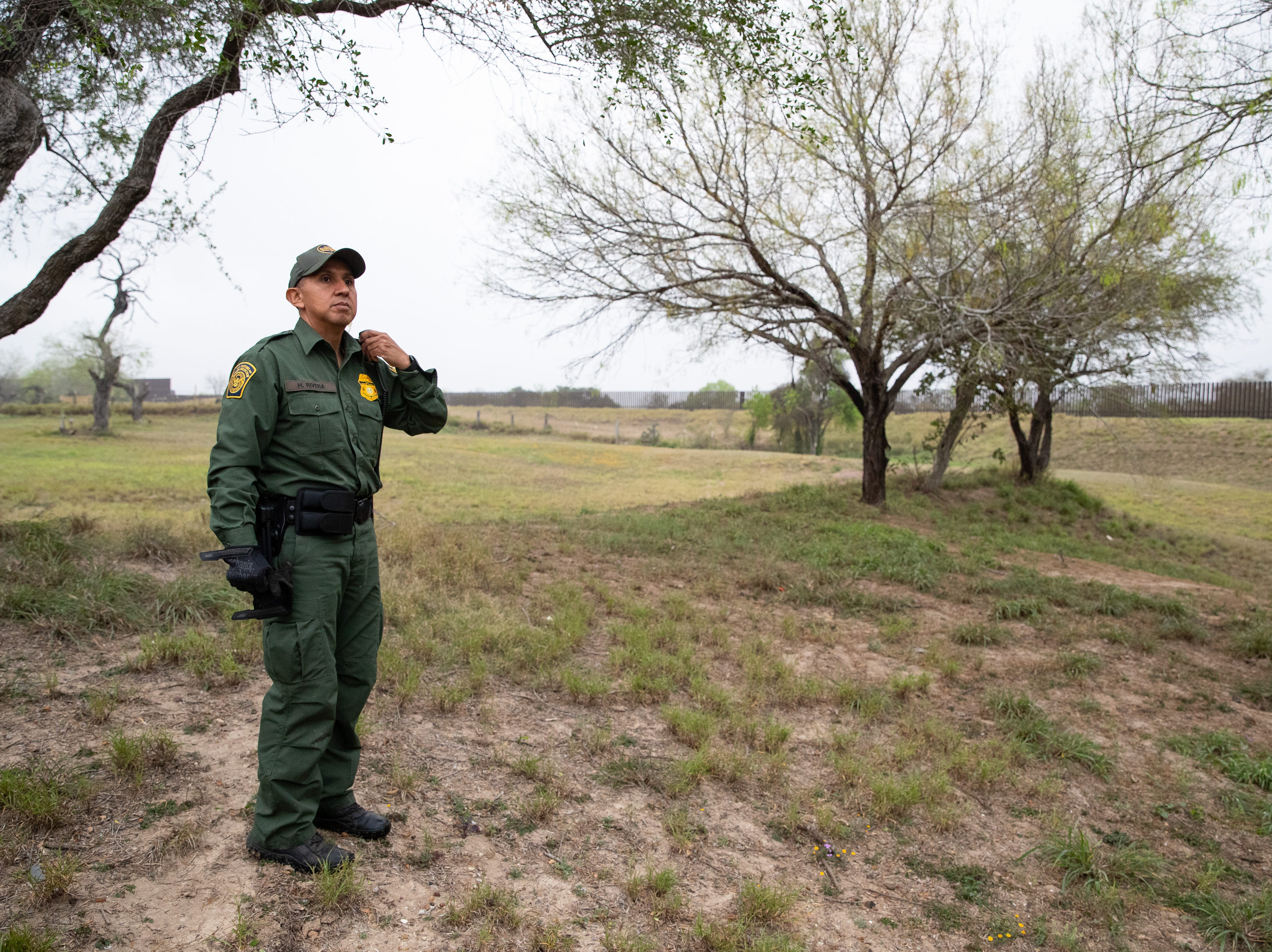 Border Patrol Agent Hermann Rivera radios to other agents as they search an area in Penitas, Texas, after a camera spotted two migrants walking in the area on Tuesday, Feb. 26, 2019.