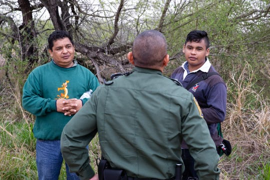 Border Patrol Agent Hermann Rivera takes a fourth-four year-old Honduran man and his 16-year-old son in to custody who had been walking lost for hours after crossing the river from Mexico near Mission TX, on Tuesday, Feb. 28, 2019.