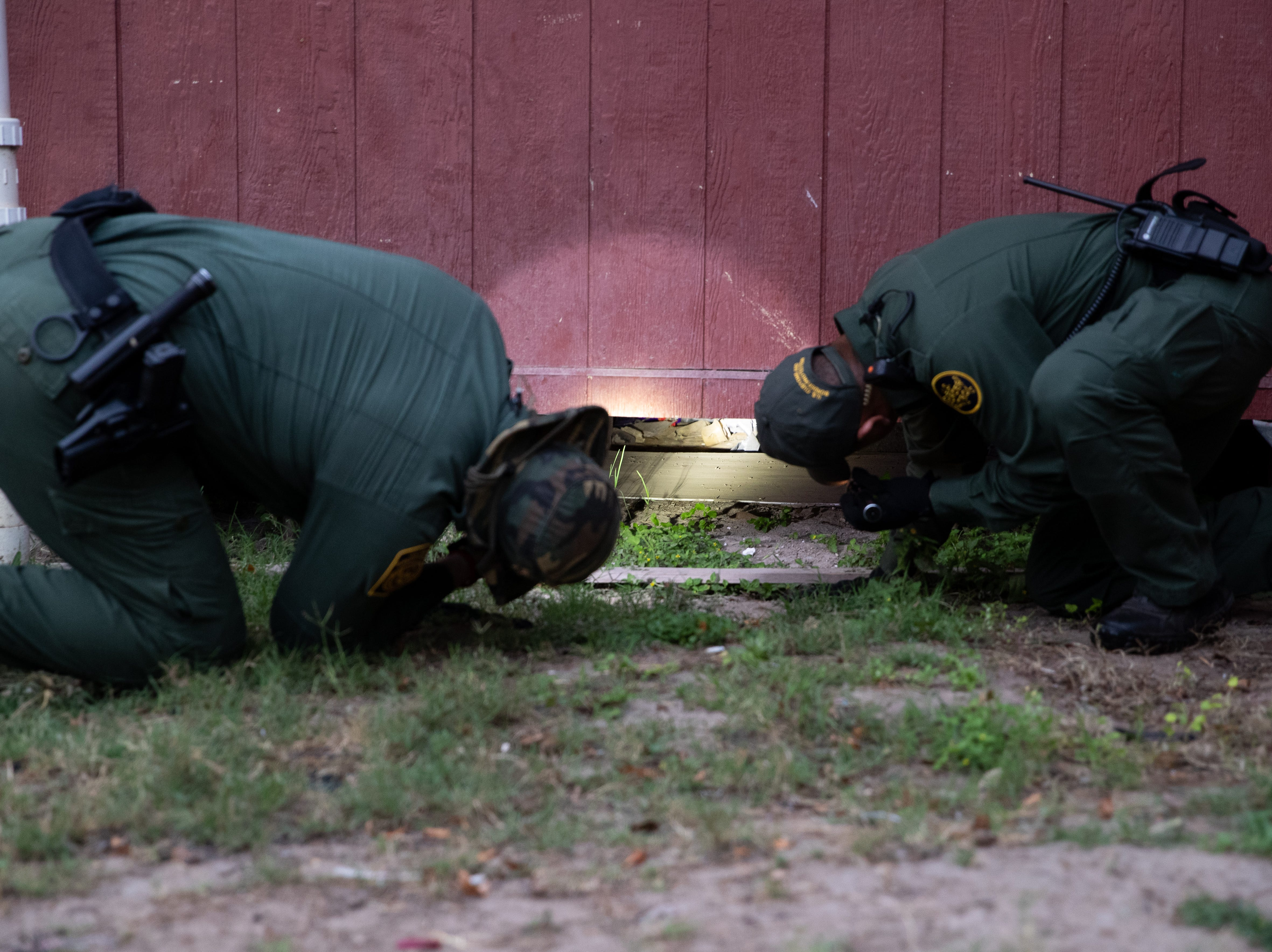 Border Patrol Agent's uses their flashlights to check underneath a home in Penitas, Texas, as they search an area after a camera spotted two migrants walking in the area on Tuesday, Feb. 26, 2019.
