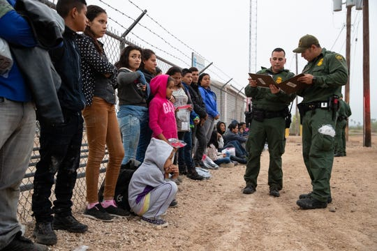 A large group of migrant family wait along the side of the road to be transported after turning themselves in to Border Patrol agents in Penitas, Texas, on Tuesday, Feb. 26, 2019.