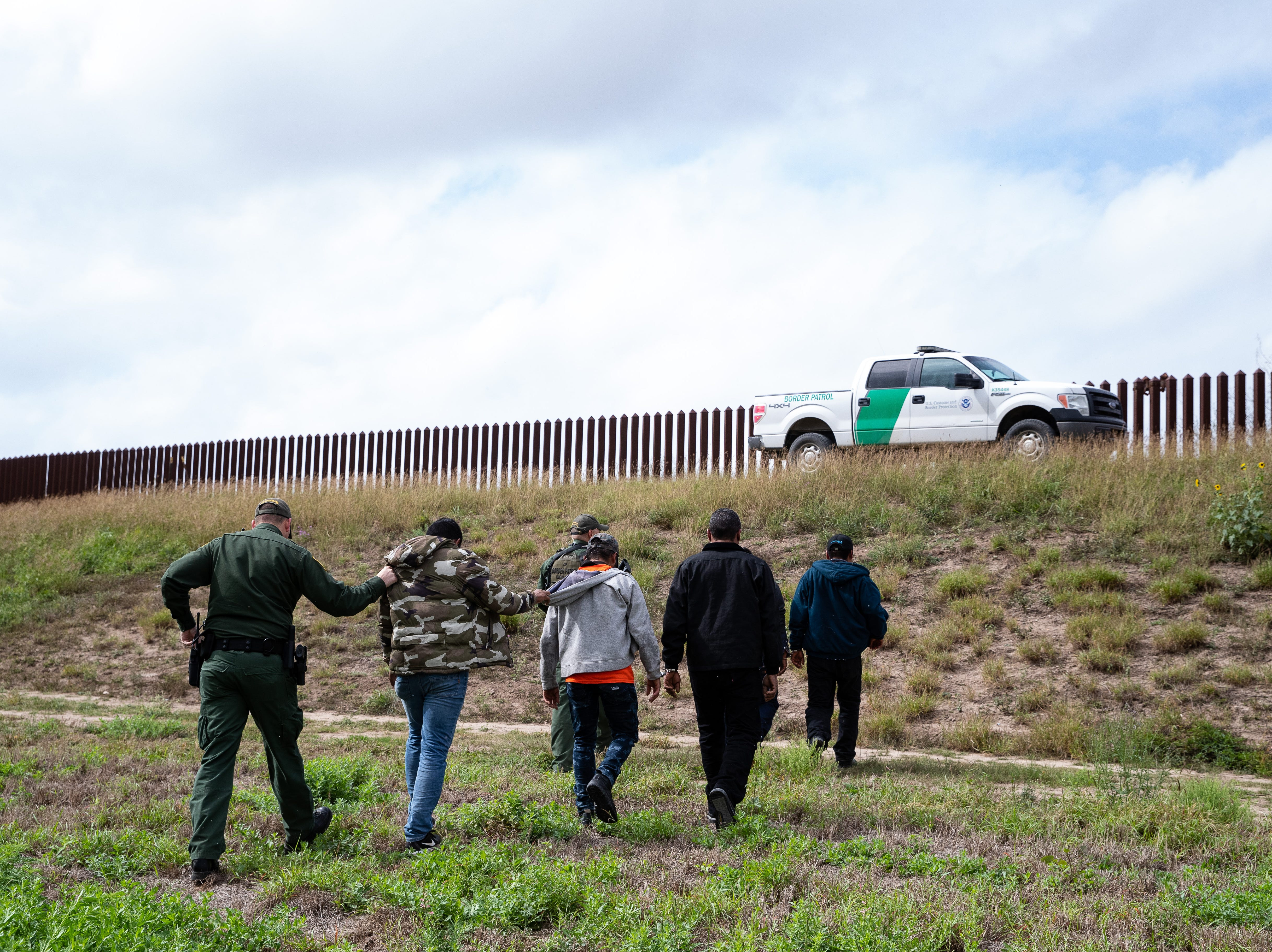 Border Patrol agents take a group of migrants in to custody  after they ran in to a field in Mission, Texas, on Tuesday, Feb. 28, 2019.