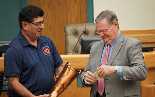Corpus Christi Mayor Joe McComb, right, prepares to make the first donation to this year's Fill the Boot campaign while retired firefighter and local MDA coordinator Carlos Torres looks on during a Feb. 26, 2019 city council meeting.