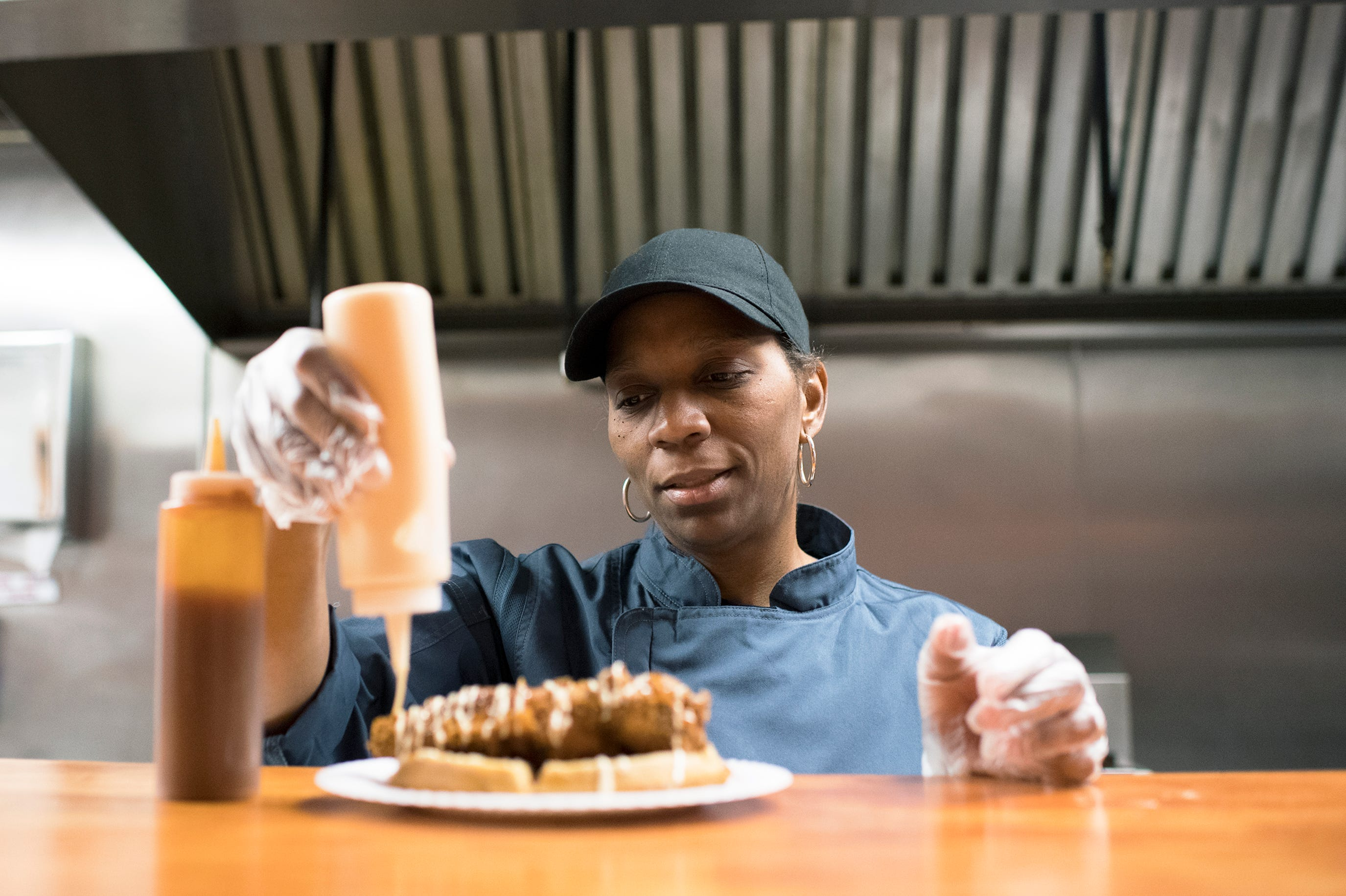 Nancy Miller, chef and owner of Taste of SOUL in Burlington City, N.J., prepares a chicken and sweet potato waffle dish. She's adding the French vanilla cream to the popular dish.