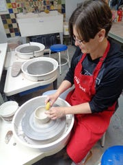 "Bonnie McNett at the potters wheel throwing a bowl during the Whistle Stop Clay Works ""Bowl-a-Thon"" Sunday, February 17"