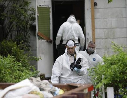 Investigators from East Brunswick Police and the Middlesex County Prosecutors Office work at the scene of a suspected homicide Tuesday, May 5, 2009 at 11 Lee Street in East Brunswick.