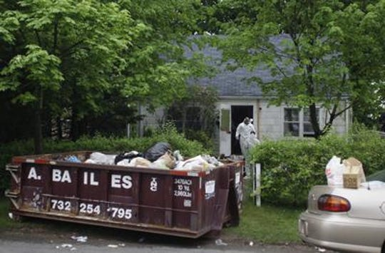 Investigators from East Brunswick Police and the Middlesex County Prosecutors Office work at the scene of a suspected homicide Tuesday, May 5, 2009 at 11 Lee Street in East Brunswick. Officers were removing debris from inside the home and placing it into the 10 cubic yard dumpster while they were conducting the investigation