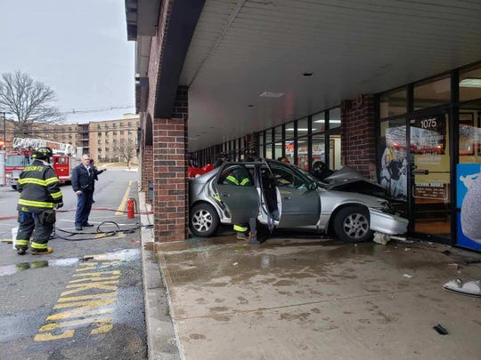 Firefighters respond to car that crashed into building at Inman Grove shopping center in Edison.