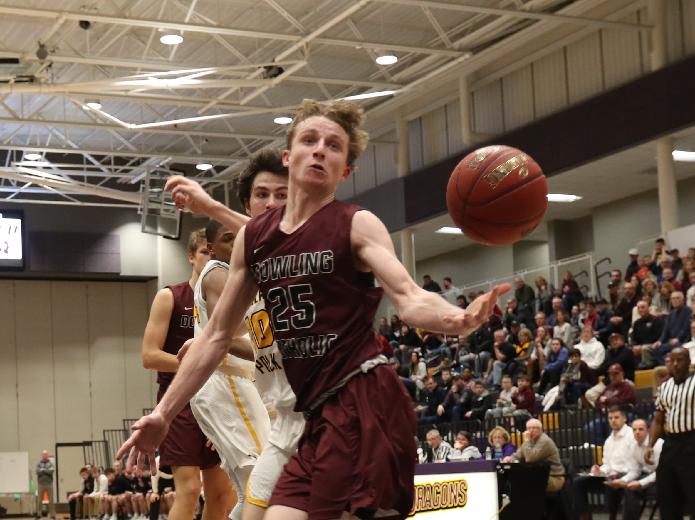 Dowling Catholic's Matt Stilwill (25) saves a ball from going out of bounds against Southeast Polk during their game at Johnston High School in Johnston, Iowa, on Tuesday, Feb. 26, 2019. Dowling won the game 44-40 to advance to state.